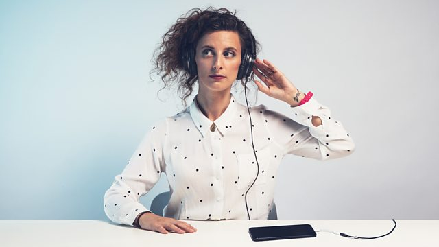 Felicity Ward wearing headphones which are connected to her smartphone