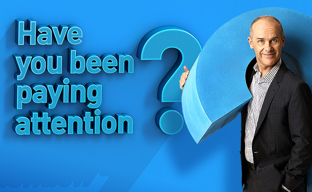 Tom Gleisner poses holding a question mark next to the Have You Been Paying Attention? logo