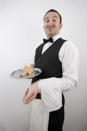 Silver service waiter with moustache and silver tray with a chicken on it